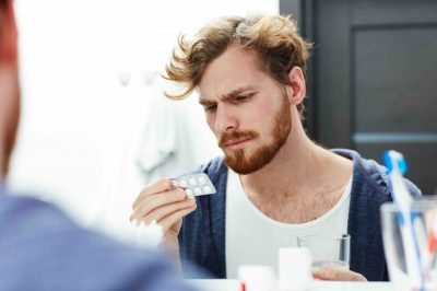 Man with headache going to take pill